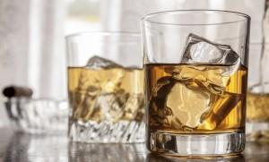 Glasses of whiskey and ice cubes on wooden surface with window back light